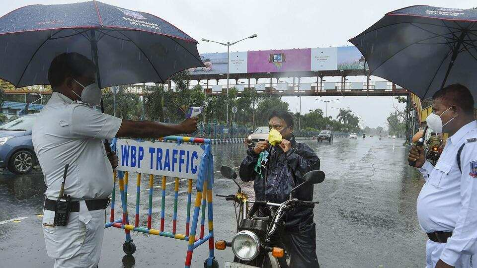 Kolkata: A police constable uses a thermal screening device on a commuter amid rain during the biweekly lockdown in the wake of Covid-19 pandemic.