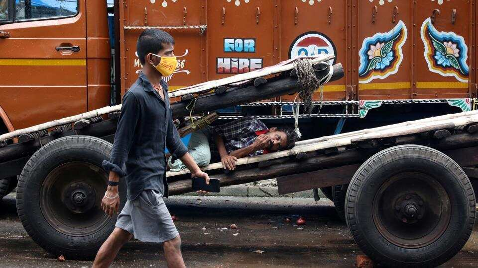 A man wearing a protective face mask walks past a labourer resting on a handcart in a closed wholesale market in West Bengal.